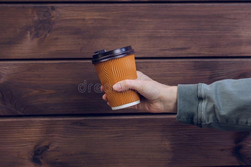 Det kaffetid för ` s! Hand för kvinna` som s rymmer den pappers- koppen av nytt kaffe mot papper för måltid för avhämtning för mö royaltyfri foto