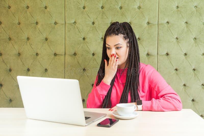 Det kan jag inte tro! Strålningskänsliga unga kvinnor med svart läsk hårstil sitter i kaféet och läser nyheter med royaltyfri foto