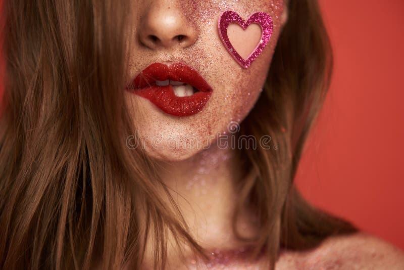Det kantjusterade fotoet av den glamor?sa modellen med glansigt bl?nker makeup inomhus arkivfoton