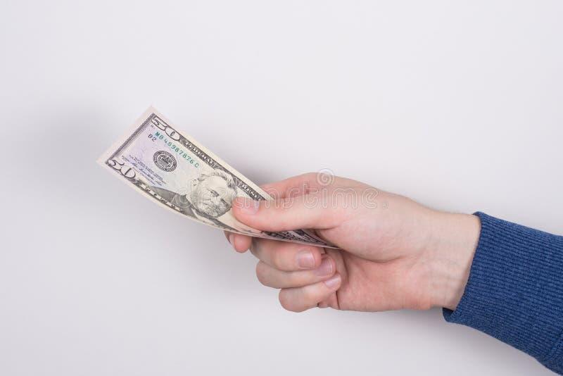 Det kantjusterade fotoet för closeupsidoprofilen av arbetarens hand som ger ett papper oss pengar, isolerade grå bakgrund royaltyfria bilder