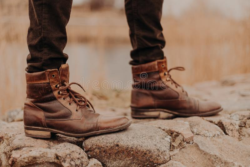 Det kantjusterade skottet av den oigenkännliga mannen bär gamla skor, har går utomhus- suddig bakgrund Kängor på stenar för begre royaltyfri fotografi
