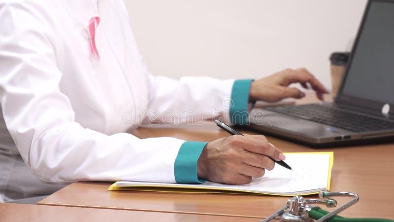 Det kantjusterade skottet av en kvinnlig doktorshandstil noterar genom att använda hennes bärbar dator på arbete royaltyfri fotografi