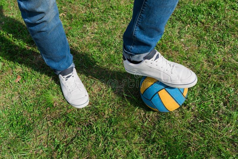 det kantjusterade skottet av mannen i jeans och sportar skor anseende med bollen royaltyfri foto