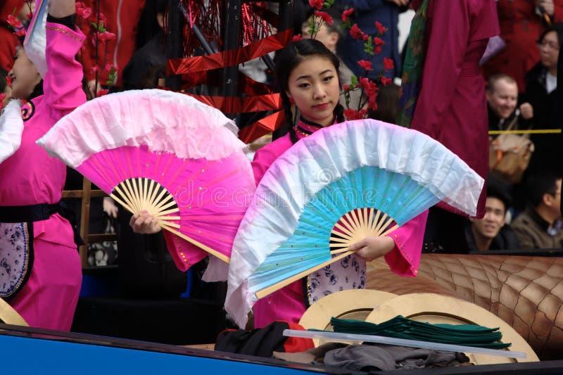 Det kinesiska nya året ståtar, flickan med fläktar royaltyfria bilder