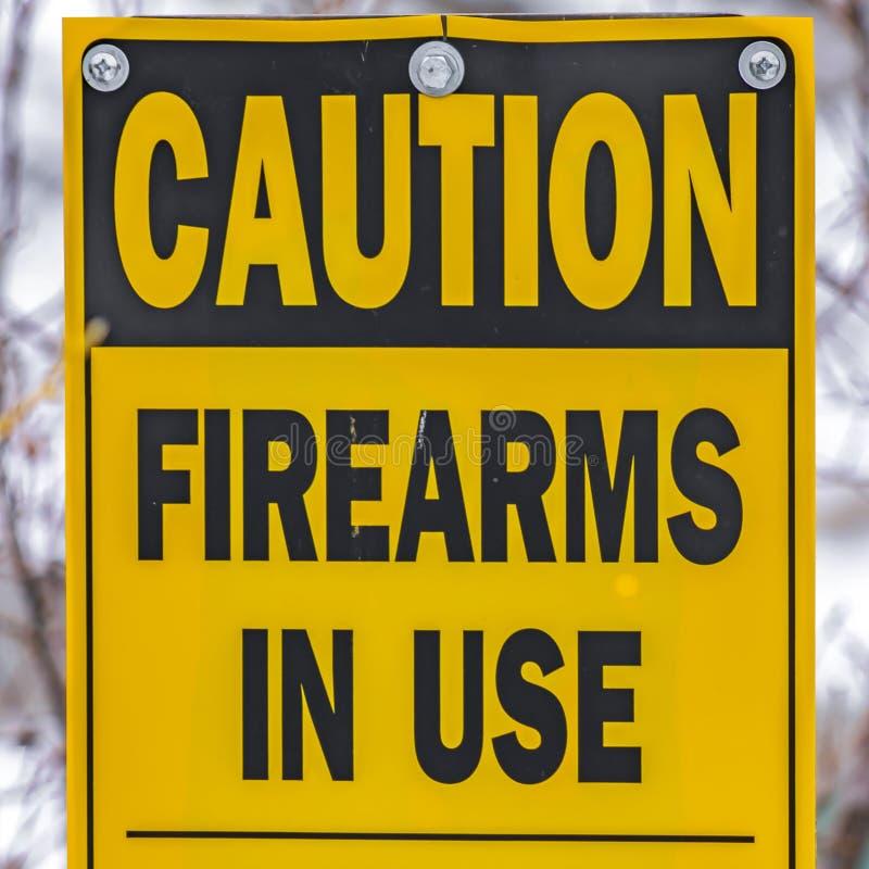 Det klara fyrkantiga slutet upp av ett gult tecken, som läser, varningsskjutvapen som är i bruk, håller ut arkivfoton