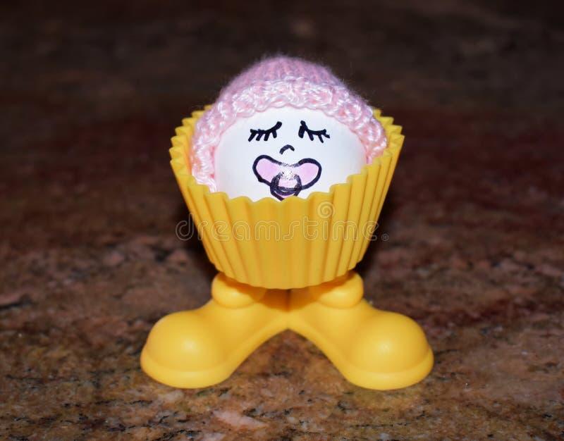 Det kokta ägget med behandla som ett barn hättan inom äggkoppen fotografering för bildbyråer