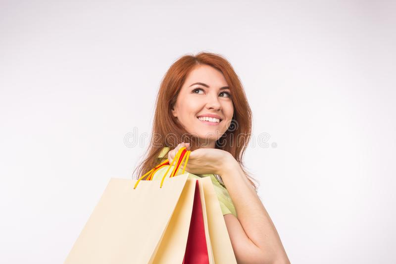 Det konsument-, försäljnings- och folkbegreppet - utforma påsar för shopping för rödhårig mankvinnan hållande arkivbilder