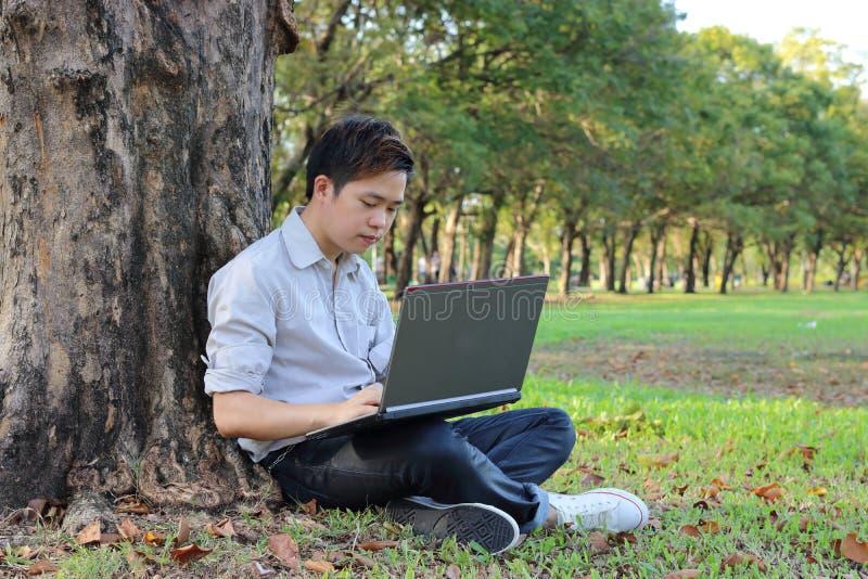 Det kopplade av barnet man använder en bärbar dator på det utomhus- parkerar Koppla av och teknologibegreppet arkivfoton