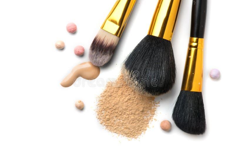 Det kosmetiska vätskefundamentet eller kräm, löst framsidapulver, olika borstar för applicerar makeup Sminktäckstiftsudd och pulv arkivbilder