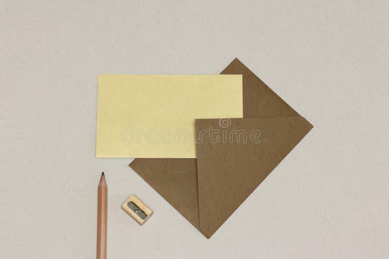 Det kraft kuvertet, det gula papperet, träblyertspennan & vässaren, på det vita skrivbordet arkivbild