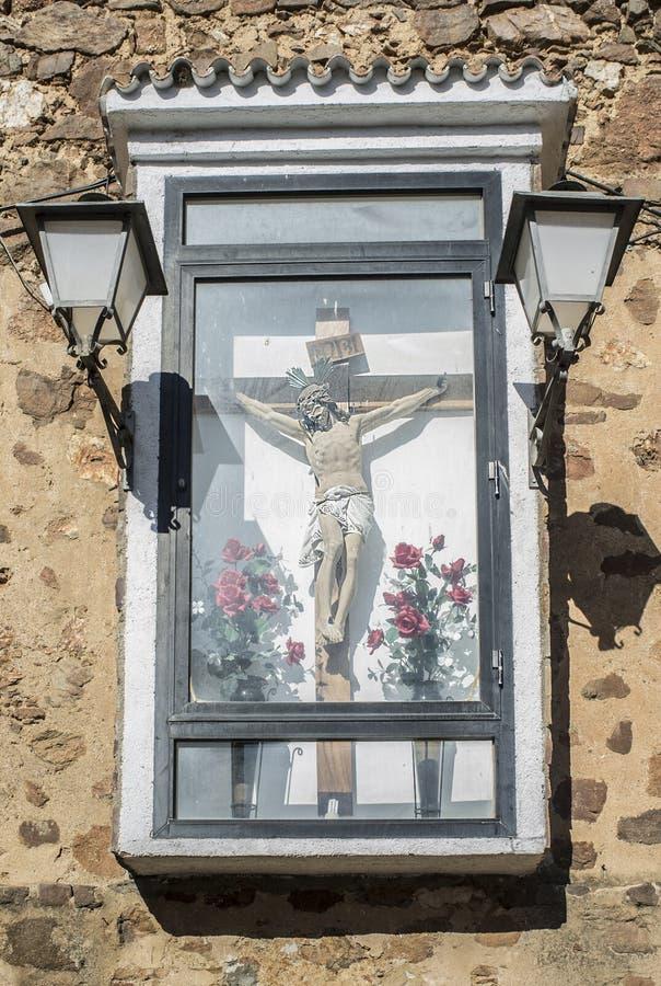 Det kristna korset står inneslutat och fäst utomhus till väggen arkivfoto