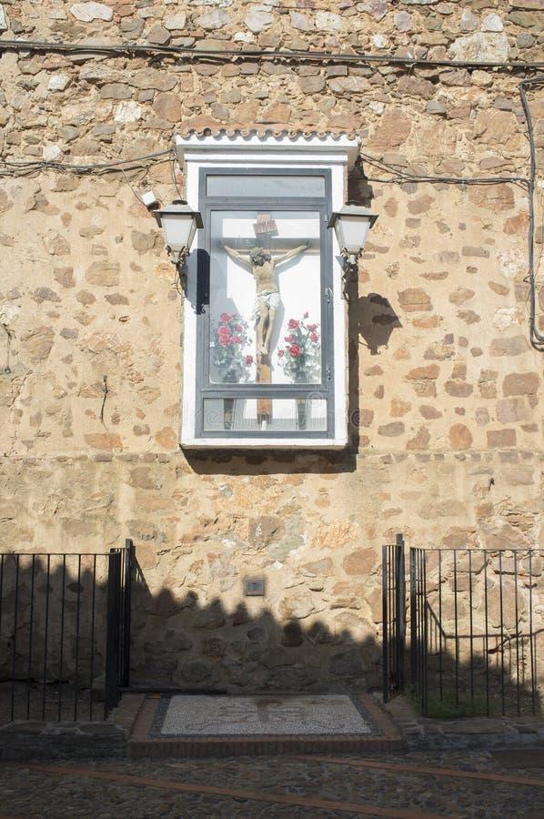 Det kristna korset står inneslutat och fäst utomhus till väggen royaltyfri foto