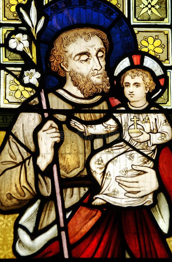 Det kulöra nedfläckade Joseph för leadlightkyrkafönstret innehavet behandla som ett barn Kristus Jesus royaltyfri bild