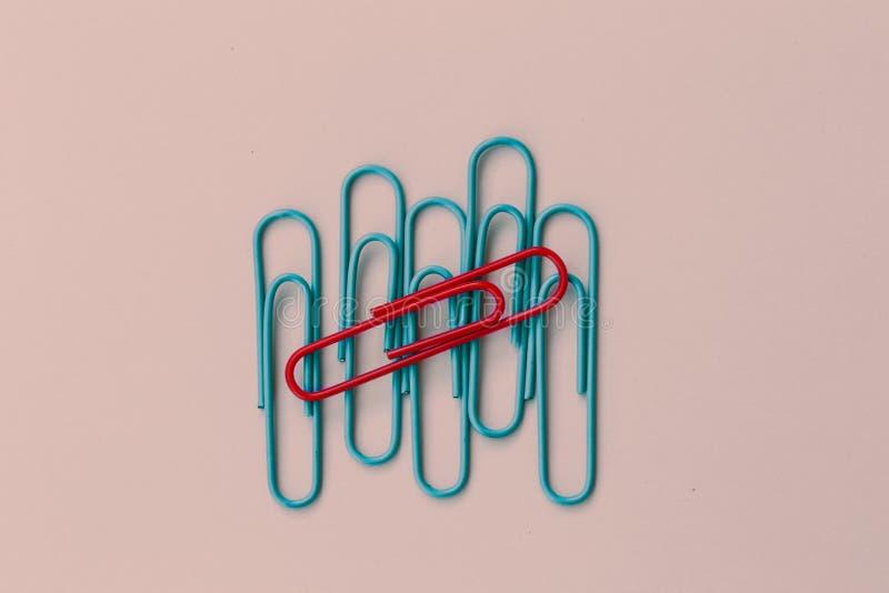Det kulöra pappers- röda gemet med en skillnad på blått fäster ihop annan MI arkivfoton