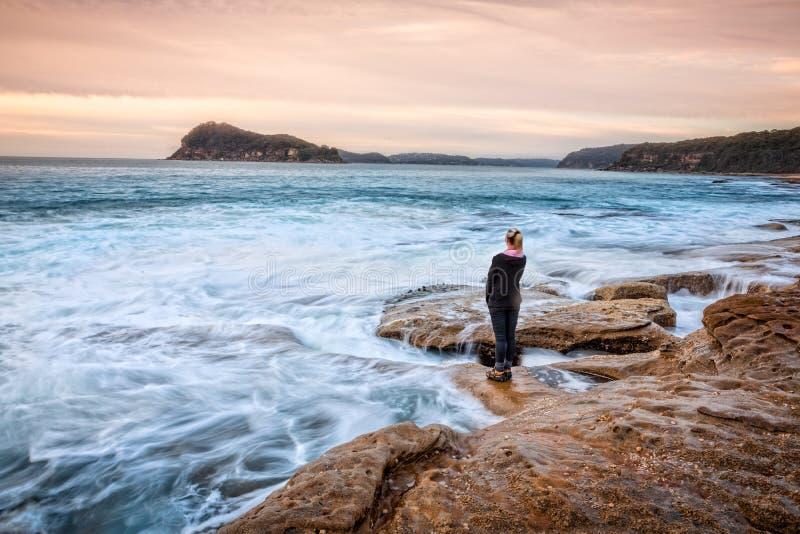 Det kvinnliga anseendet på vaggar att låta kust- vågor tvätta upp till hennes fot royaltyfri fotografi