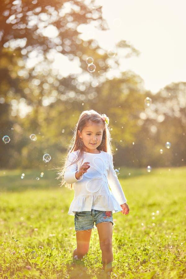 Det kvinnliga barnet tycker om att jaga såpbubblor royaltyfri foto