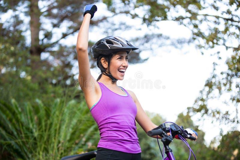Det kvinnliga cyklistanseendet med mountainbiket parkerar in royaltyfria foton