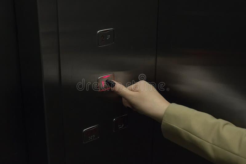 Det kvinnliga fingret trycker på knappen på hissen för att gå till det första golvet arkivfoton