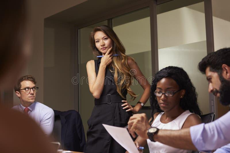 Det kvinnliga framstickandet står tänka på ett aftonaffärsmöte arkivfoton