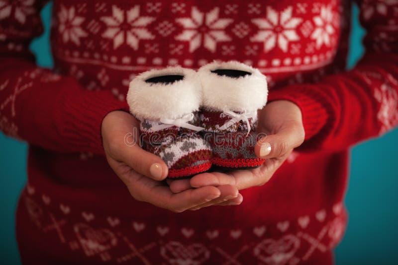 Det kvinnliga innehavet behandla som ett barn julskor arkivfoto