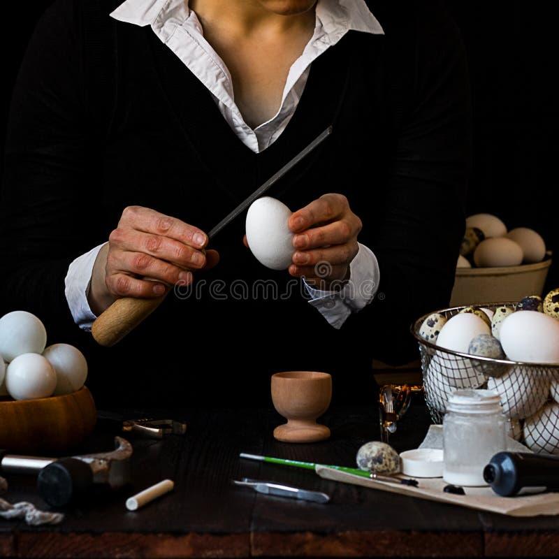 Det låga nyckel- fotoet av händer i svart med vita manschetter som gör ägget, bunke med, knackar pongbollar, instrument och målar arkivbilder