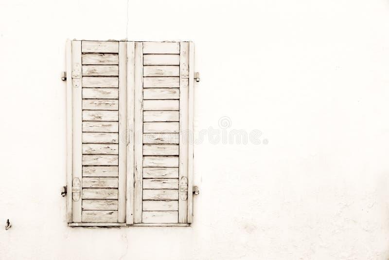 Det lantliga gamla grungy och red ut vita gråa trästängda fönstret stänger med fönsterluckor med skalningsmålarfärg royaltyfri foto