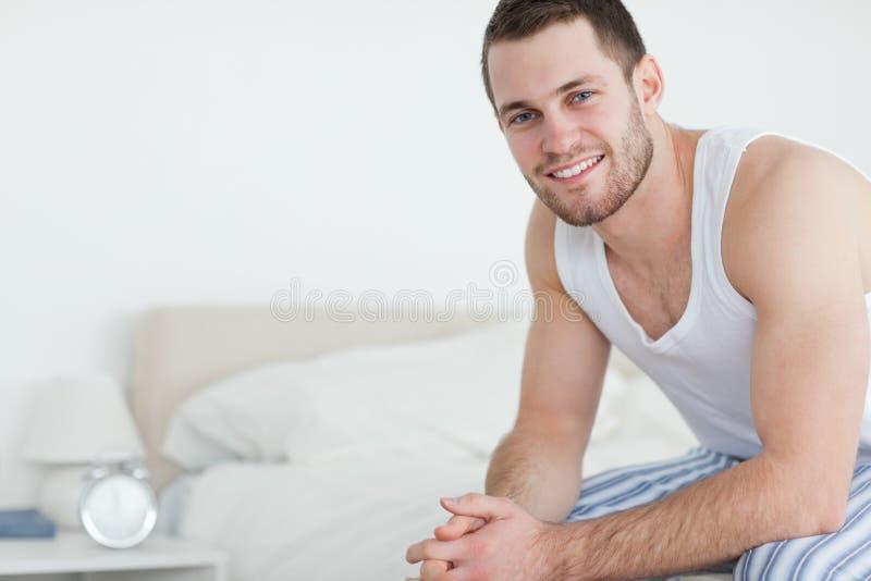 Det le barn bemannar sammanträde på hans säng arkivbild