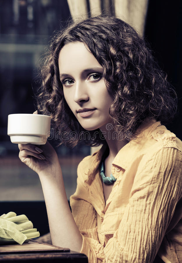 Det ledsna barnet danar kvinnan som dricker te på restaurangen arkivfoto