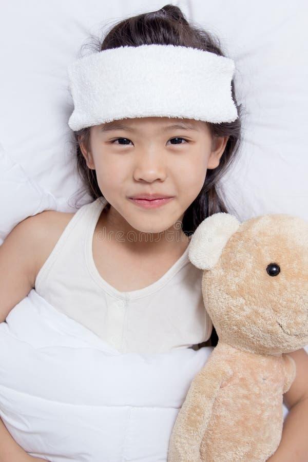 Det lilla asiatiska barnet har feber, och lägga på sängen, få väl arkivfoto