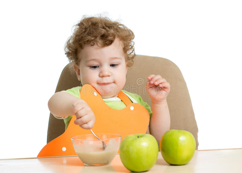 Det lilla barnet äter med skedsammanträde på tabellen med arkivfoton