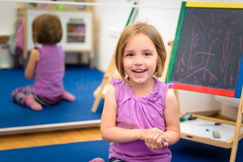 Det lilla barnet drar med färgkrita på kritabrädet arkivfoto