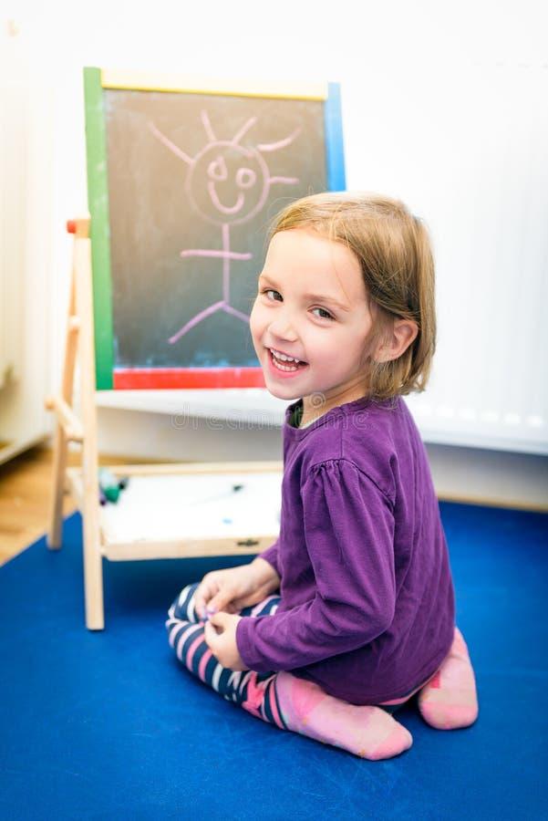 Det lilla barnet drar med färgkrita på kritabrädet royaltyfria bilder