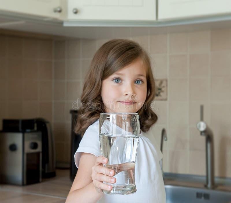 Det lilla barnet dricker rent vatten hemma, slutet upp Den Caucasian gulliga flickan med långt hår rymmer ett vattenexponeringsgl arkivfoto