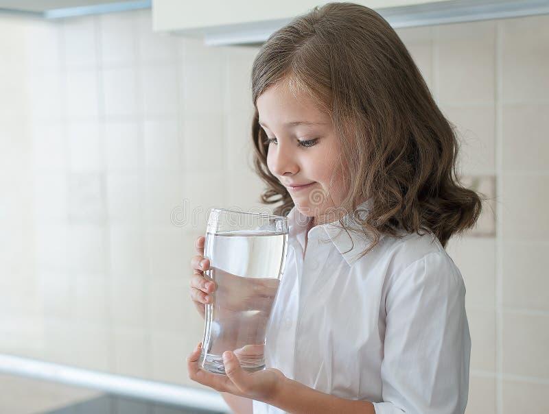 Det lilla barnet dricker rent vatten hemma, slutet upp Den Caucasian gulliga flickan med långt hår rymmer ett vattenexponeringsgl arkivbild