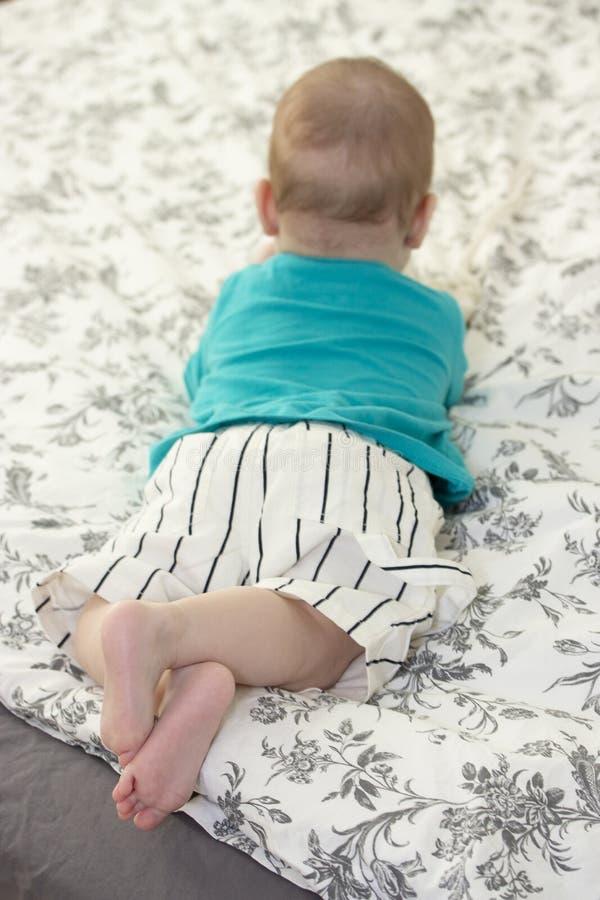 Det lilla barnet ligger på sängen, sikt från baksidan Behandla som ett barn pojkeflickan som vilar med korsad kal fot royaltyfri fotografi