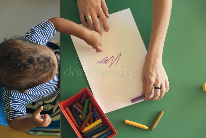 Det lilla barnet och modern drar på ett papper royaltyfri foto