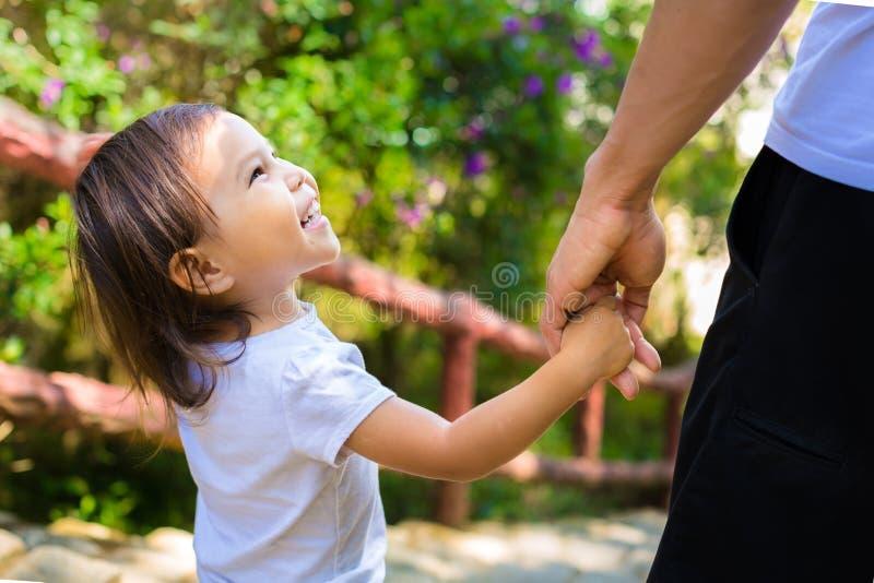 Det lilla barnet ser upp lyckligt på hennes fader, medan de går till och med parkerainnehavhänderna royaltyfri fotografi