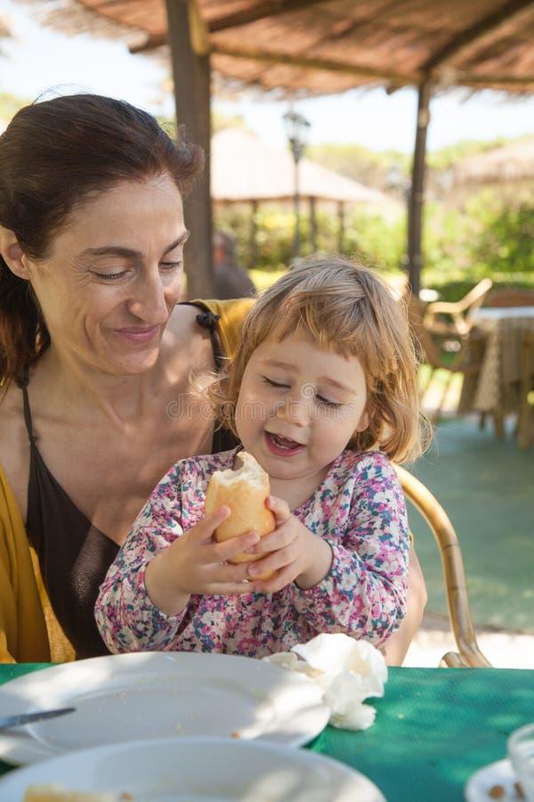 Det lilla barnet som äter brödsammanträde på kvinna, lägger benen på ryggen arkivfoton