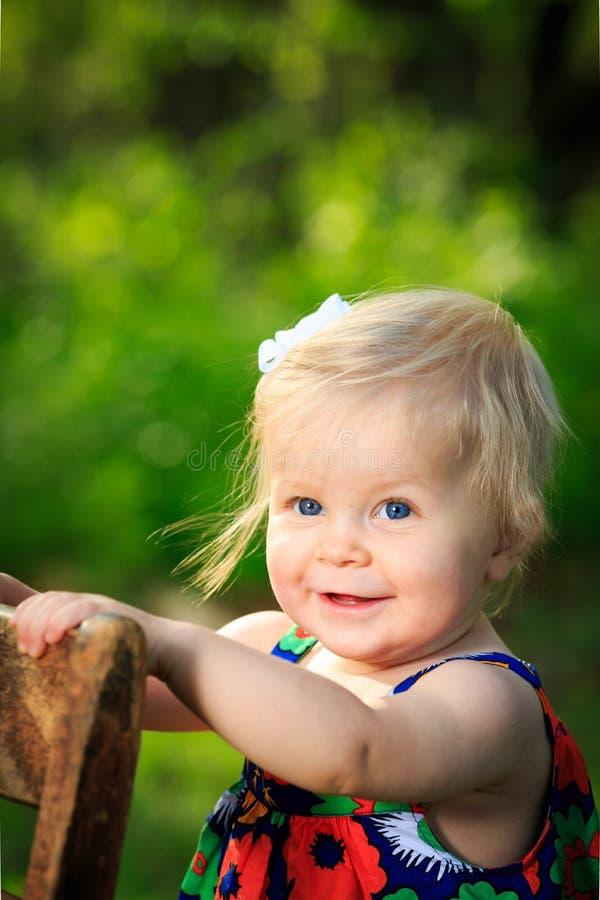 Det lilla caucasian lilla barnet står genom att använda stol för service utanför royaltyfri fotografi