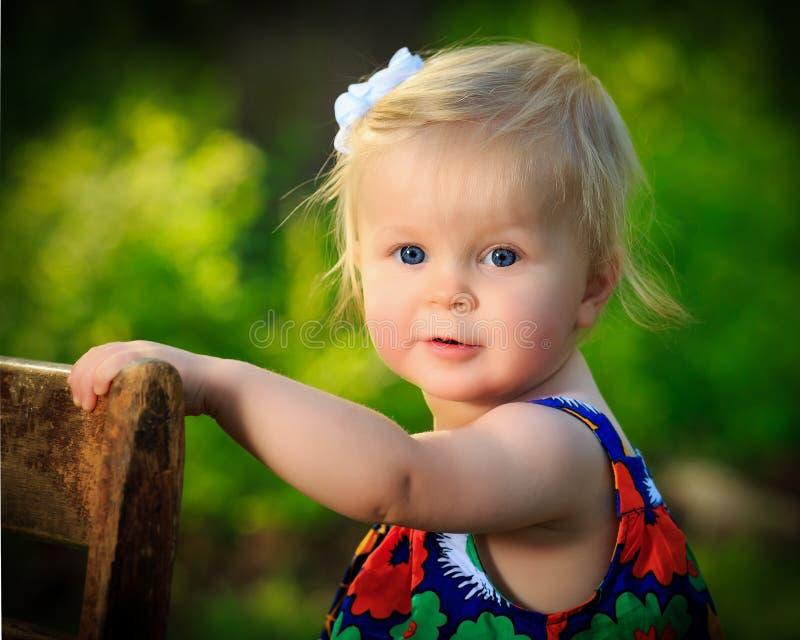 Det lilla caucasian lilla barnet står genom att använda stol för service utanför royaltyfria foton