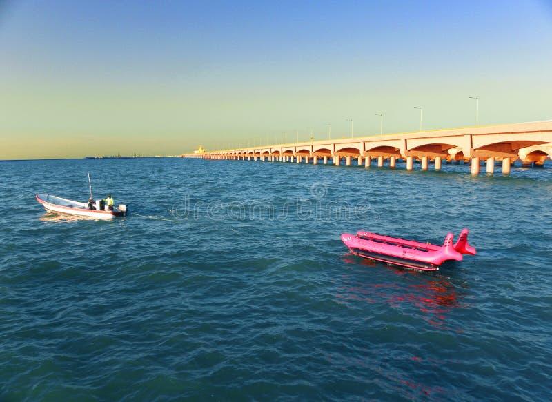 Det lilla fartyget i sidan av de långa bågarna ansluter i Progreso port, Yucatan, Mexico arkivbild