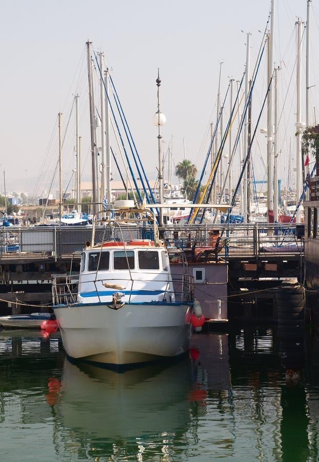 Det lilla fartyget på en kajbakgrund arkivfoton