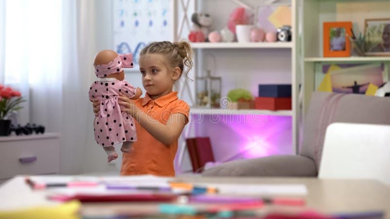 Det lilla flickainnehavet och att se leksaken behandla som ett barn, flickaktig fritid, barndomlycka arkivfoto