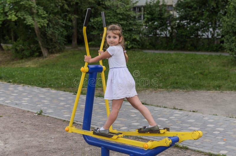 Det lilla härliga flickabarnet kopplas in på simulatorer på lekplatsen för kondition i gatan royaltyfria foton
