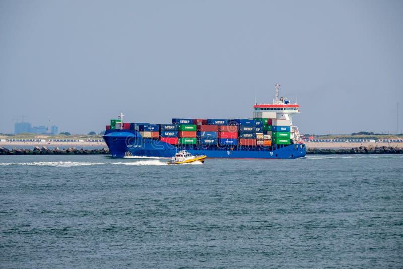 Det lilla pilot- fartyget passerar det sjögående behållareskeppet arkivfoton