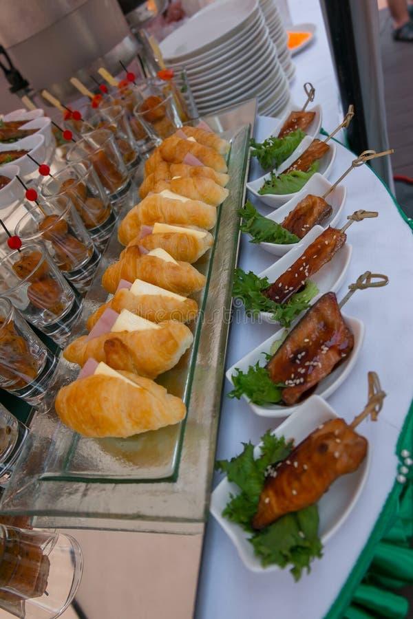 Det livsmedel som ligger på bordet omfattar krossanter, korv, grillat svin royaltyfria foton
