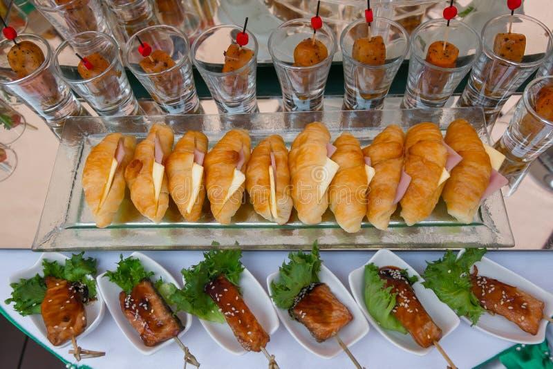 Det livsmedel som ligger på bordet omfattar krossanter, korv, grillat svin royaltyfri foto