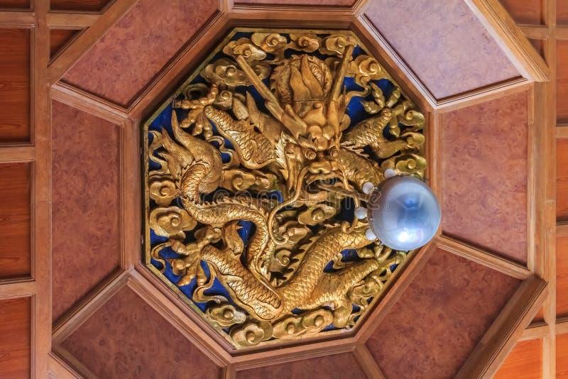 Det ljusa fasta tillbehöret av en utsmyckad guld- drake som jagar pärlan, grundar royaltyfria foton