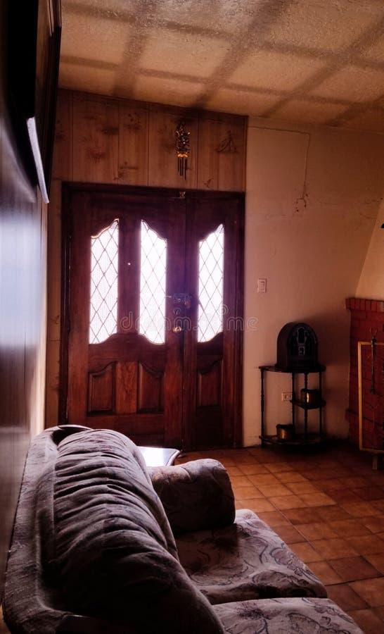 Det ljusa hemmet, beskådar inomhus med en dörr och en soffa arkivbilder