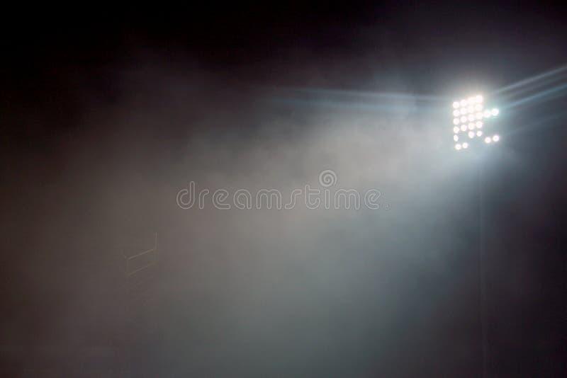 Det ljusa tornet tände på en stadion under nightime Stadionen tänder mot bakgrund för mörkernattsky Stadionljus och rök arkivbild